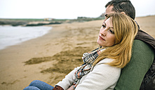 Couple in love sitting on the beach in winter - DAPF00594
