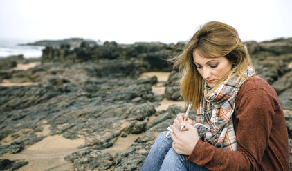 Woman with notebook sitting on rocks on the beach in winter - DAPF00600