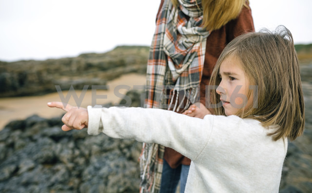 Girl with mother pointing her finger on the beach in winter - DAPF00603