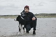 Netherlands, Schiermonnikoog, man with Border Collie on the beach - DWF00288