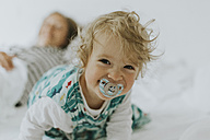 Portrait of happy little girl with mother in bed - DWF00291
