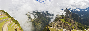 Peru, Andes, Urubamba Valley, Machu Picchu with mountain Huayna Picchu in fog with tourists - FOF08816
