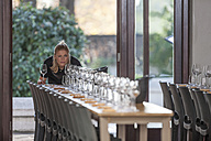 Waitress lining up row of wine glasses at restaurant - ZEF12748