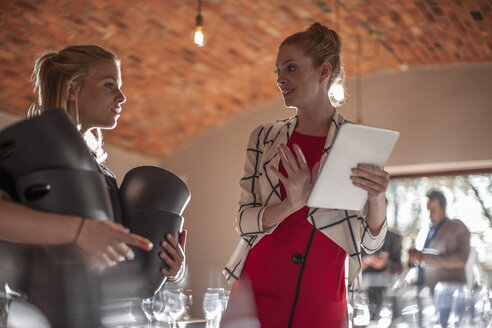 Woman with tablet talking to waitress in a restaurant - ZEF12754