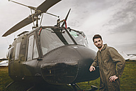 Man in overall standing next to a helicopter - MADF01309