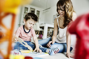 Mother and son plying in living room - JATF00957
