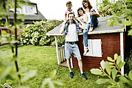 Happy family sitting on roof of their garden shed - JATF00963