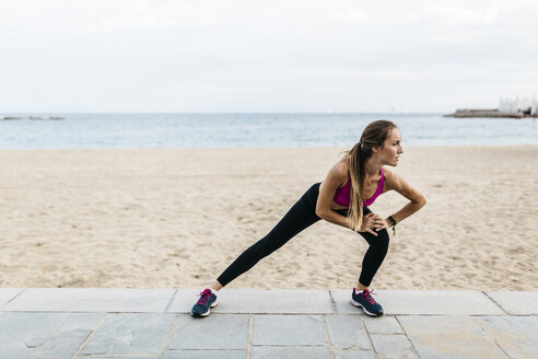 Young woman stretching and warming up for training at the beach - GIOF01729