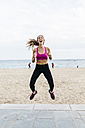 Young sportive woman jumping on the beach, laughing - GIOF01732