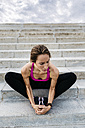 Young woman sitting on stairs after training, stretching legs - GIOF01741