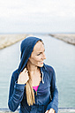 Woman with hooded jacket standing at the beach - GIOF01750