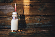 Glass bottle of almond milk on wood - GIOF01756