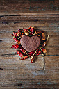 Heart-shaped chocolate shortbread surrounded by red dried chili pods on wood - GIOF01759
