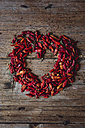 Heart shaped with red dried chili pods on wood - GIOF01762