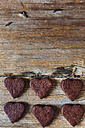 Six heart-shaped chocolate shortbreads in rows on wood - GIOF01768
