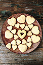 Wooden plate of heart-shaped shortbreads on wood - GIOF01771