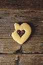 Bitten heart-shaped Shortbread with chocolate filling on wood - GIOF01777