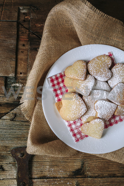 Heart-shaped shortbreads sprinkled with icing sugar on napkin and plate - GIOF01780 - Giorgio Fochesato/Westend61