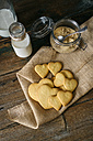 Heart-shaped shortbreads on jute, glass bottle of milk and preserving jar of brown sugar - GIOF01786