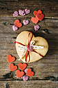 Stack of heart-shaped shortbreads tied with lace and ribbon on wood - GIOF01789