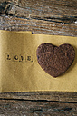 Heart-shaped chocolate Shortbread on paper with the word 'love' - GIOF01798