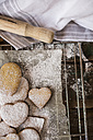 Heart-shaped shortbreads sprinkled with icing sugar and cookie cutter on parchment paper - GIOF01801
