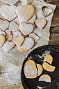 Heart-shaped shortbreads sprinkled with icing sugar on parchment paper and baking pan - GIOF01804
