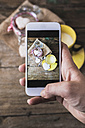 Woman taking a photo of shortbreads and cup of milk with her smartphone, close-up - GIOF01810