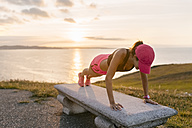 Young woman doing strength training on a bench at the sea - MGOF02893