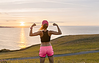 Young woman looking at the sea after workout, flexing muscles - MGOF02899