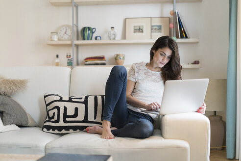 Woman sitting on couch at home using laptop - KKAF00384