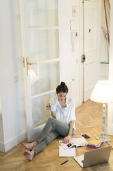 Young woman sitting on the floor with coffee mug, catalogue and laptop - KKAF00390