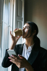 Young busnesswoman at the window drinking coffee and holding cell phone - VABF01098