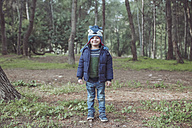 Portrait of smiling boy wearing wooly hat in forest - RTBF00624