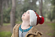 Boy wearing wooly hat in forest looking up - RTBF00630