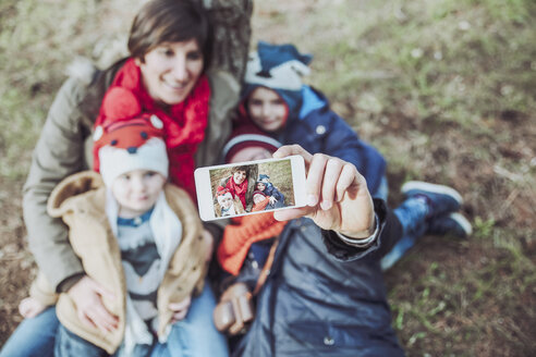 Family taking a selfie with smartphone in forest - RTBF00636