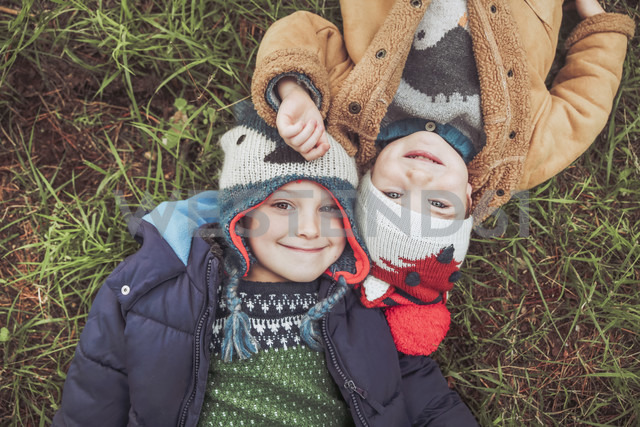 Two boys wearing wooly hats lying in grass - RTBF00648 - Retales Botijero/Westend61