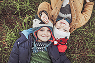 Two boys wearing wooly hats lying in grass - RTBF00648