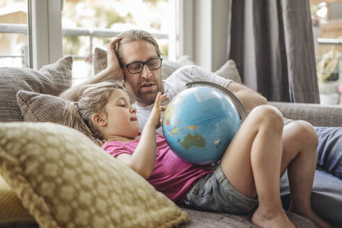Father and daughter lying with globe on sofa - JOSF00485