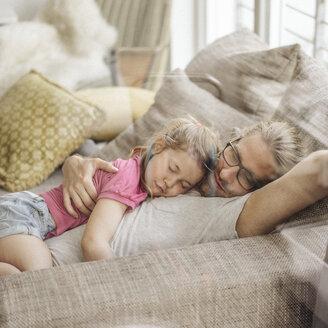 Father relaxing with daughter on sofa - JOSF00488