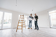 Architect checking construction plan with owner of the new home - JOSF00490