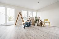 Couple sitting on floor of their new home among moving boxes - JOSF00502