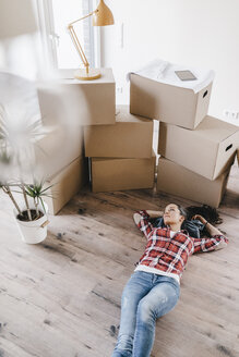 Mature woman moving house, lying on floor, thinking - JOSF00520
