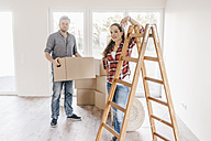 Couple moving house, carrying boxes in new home - JOSF00529