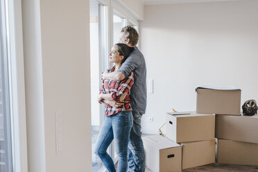 Happy couple standing at window of their new home - JOSF00544