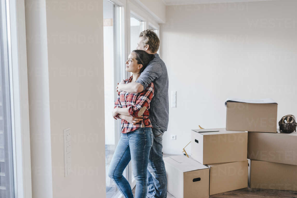Happy couple standing at window of their new home - JOSF00544 - Joseffson/Westend61