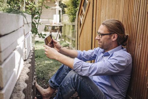 Man relaxing in garden using tablet - JOSF00568