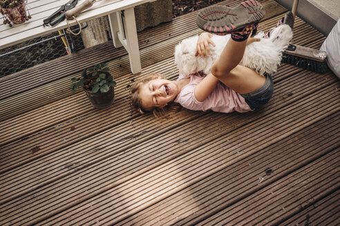 Happy girl playing with dog on wooden terrace - JOSF00571