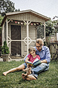 Father reading book with daughter in garden - JOSF00574