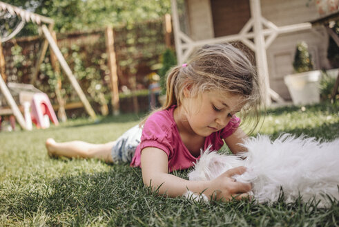 Girl lying in garden with dog - JOSF00577